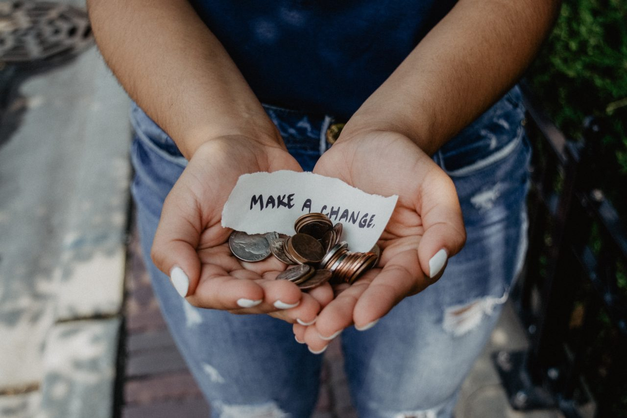 Photo of person holding their hands out with a note saying Make A Change.